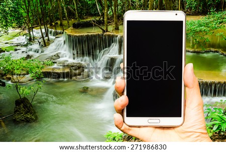 Woman hand holding smartphone against on nature background soft focus. - stock photo