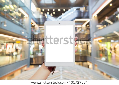 Woman hand holding tablet isolated white screen in foods zone on blurred shopping centre background, concepts of online shopping through digital smartphone, mobile or tablet device  - stock photo