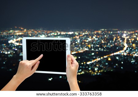 woman hand holding the phone tablet on night city bokeh background - stock photo