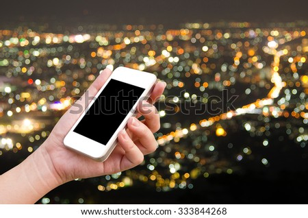 woman hand holding the phone tablet with night city bokeh background - stock photo