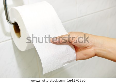 Woman hand holding the roll of toilet paper - stock photo