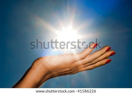 Woman hand holding the sun on a blue sky background - stock photo