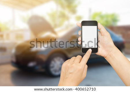 woman hand holding,using and touch smart phone,cell phone,mobile over blurred image of broken black car : concept calling mechanic service from repair shop - stock photo