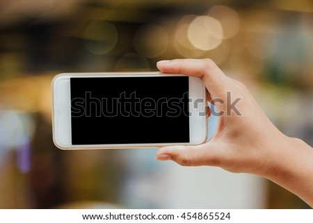 woman hand holding, using mobile smart phone with black blank screen for text in blurred bokeh of supermarket : hand using mobile isolated with clipping path