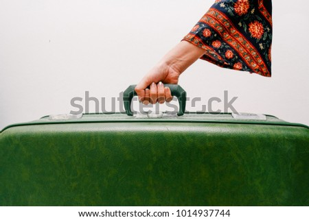 woman hand holding vintage suitcase on white background.