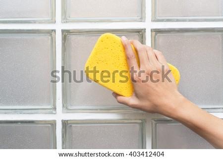 woman hand in yellow glove with sponge on glass blocks - stock photo