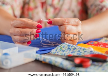 Woman hand Insert a thread in a needle