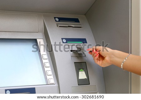 woman hand inserting credit card to ATM - stock photo