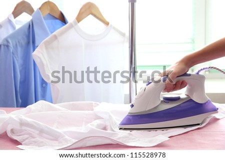 Woman hand ironing a shirt, on cloth background - stock photo
