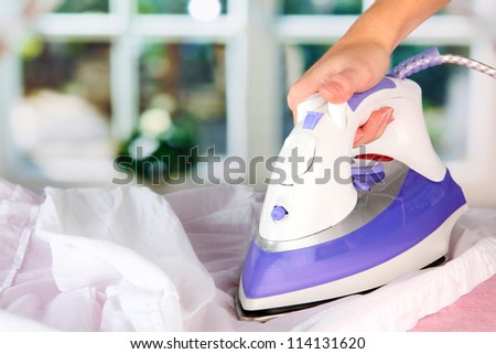 Woman hand ironing a shirt, on window background - stock photo