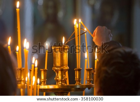 Woman hand lighting candles in a church. - stock photo