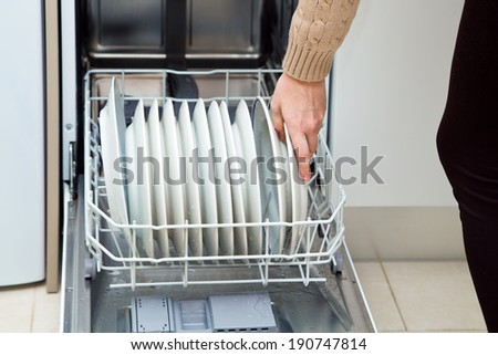 woman hand loading dishes to the dishwasher /dishwasher at the kitchen/ - stock photo