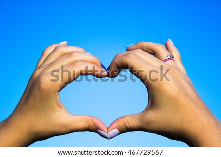 Woman hand making love sign on the nature sky background
