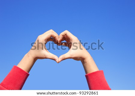 Woman hand making sign Heart in red cloth over the sky - stock photo