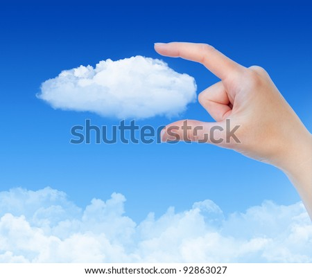 Woman hand measures the cloud against blue sky with clouds. Concept image on cloud computing and eco theme.