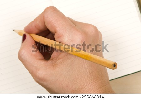 Woman hand notebook with pencil  write note - stock photo