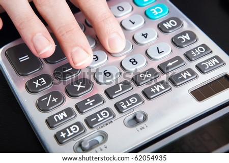 Woman hand on a digital calculator - stock photo