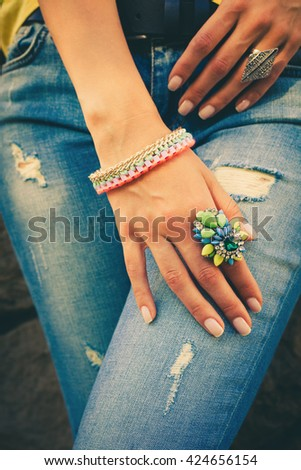 woman hand on blue jeans with big colorful ring and bracelet summer trendy bijou - stock photo