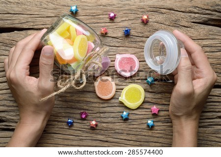woman hand open glass bottle of jelly candy dessert on wooden background - stock photo