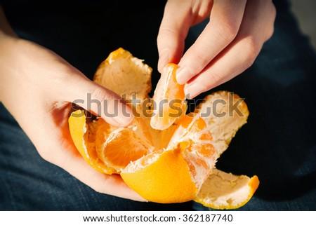 Woman hand peeling ripe sweet tangerine, close up - stock photo