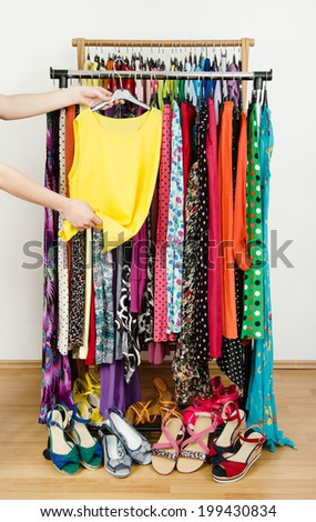 Woman hand picking up a yellow blouse to wear. Summer dresses and sandals in a wardrobe. Dressing closet with colorful clothes and shoes nicely arranged on a rack. - stock photo