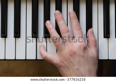 Woman hand playing piano music.