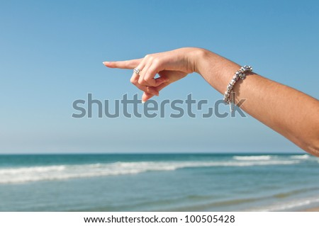 Woman hand pointing out to sea - stock photo