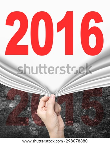 Woman hand pulling new 2016 white curtain covering old 2015 on dark mottled concrete wall. - stock photo