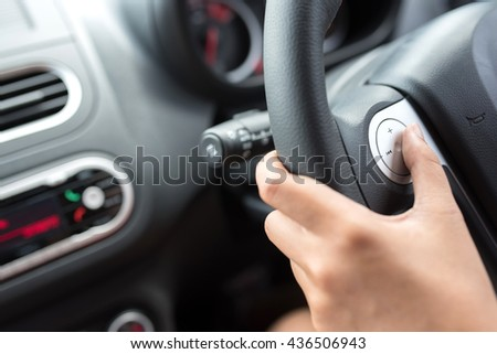 woman hand pushes the volume control button on a steering wheel.select focus Finger and button.