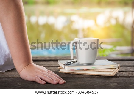 Woman hand put down beside coffee cup and notebooks on rustic wood bench with rural lake view in morning time on weekend