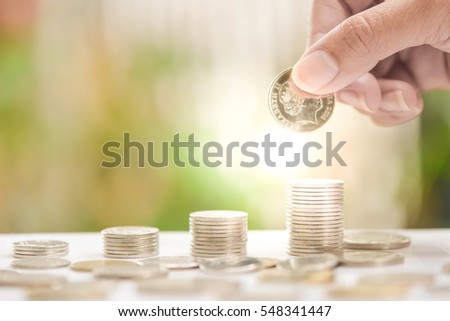 Woman hand putting coin to growing coins stacks - Concept of saving money