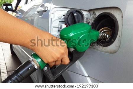 Woman hand refilling the car with fuel  - stock photo