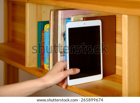 Woman hand selecting generic tablet from a bookshelf - stock photo