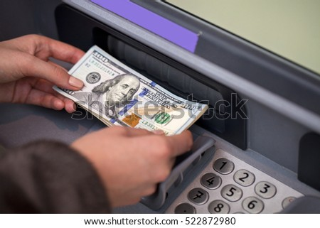 Woman hand showing dollar banknotes in front of the red atm