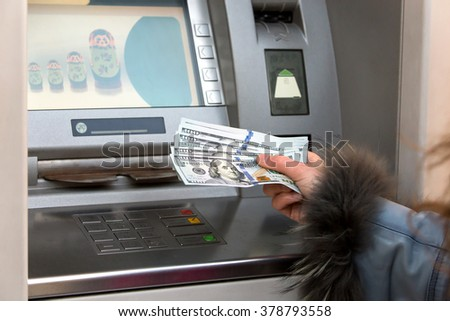 woman hand showing hundred dollar banknotes in front of the atm - stock photo