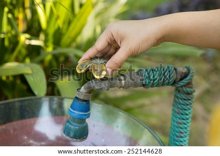 Woman hand shut the faucet, prevent from leaking waste - stock photo