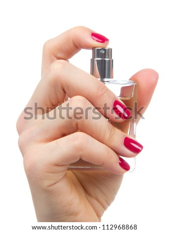 Woman hand spraying perfume. Focus on hand with red manicure and perfume bottle isolated on a white background - stock photo