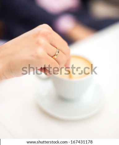woman hand stir coffee in cafe - stock photo