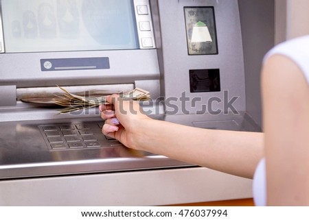 woman hand take away dollar banknotes in front of the atm