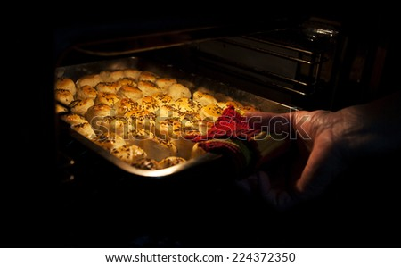 Woman hand taking out hot cakes from oven - stock photo