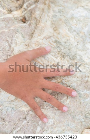 Woman hand touch on the stone background