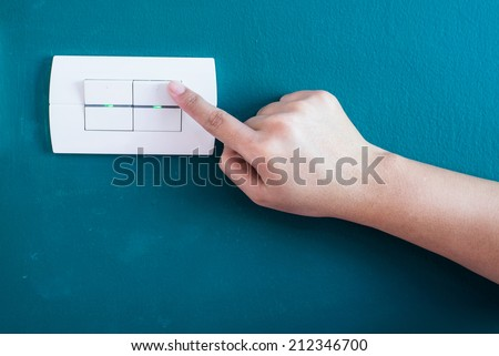 Woman hand turning operating a wall switch - stock photo