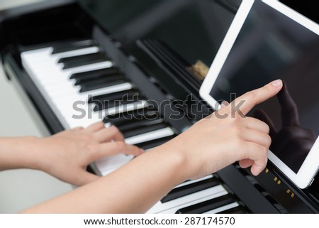 Woman hand use tablet and  playing piano music - stock photo