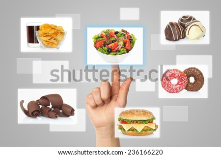 Woman hand uses touch screen interface with food on grey background  - stock photo