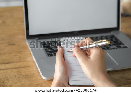 Woman  hand using a pencil noting over laptop - stock photo