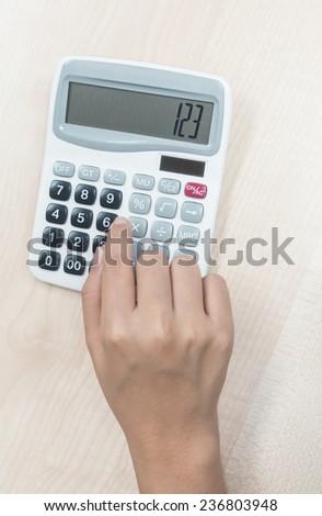 Woman hand using calculator - stock photo