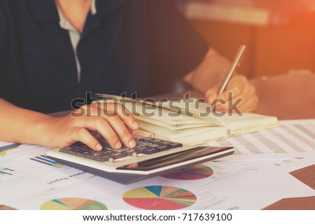 woman hand using calculator and writing make note with calculate,business concept
