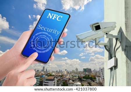 woman hand using smart phone control the CCTV , near field communication concept  - stock photo