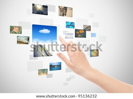 Woman hand using touch screen interface with pictures in frames. - stock photo