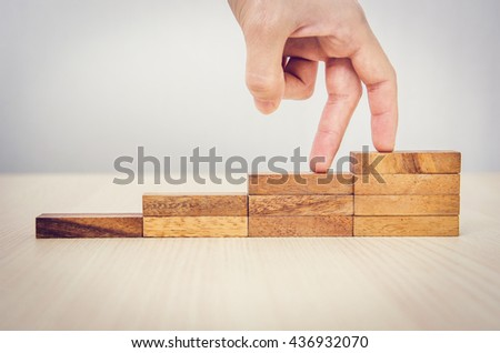 Woman hand walking his fingers up wooden steps on the way to success and aspiration. - stock photo